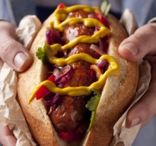 Chorizo hot dog with red peppers and onions.