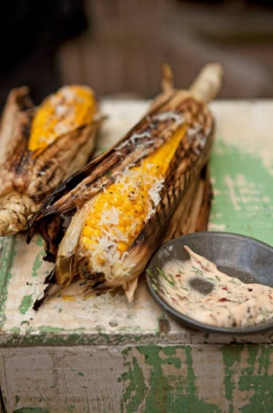 Grilled corn cobs in the husk.