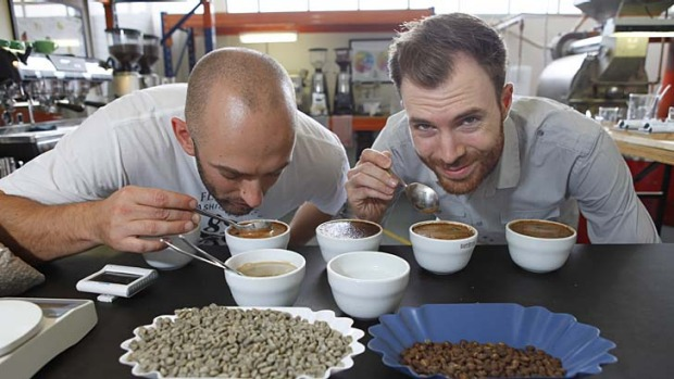 Barista champion Caleb Podhaczky and judge Ben Bicknell test Guatemala coffee beans, which will be featured at the ...