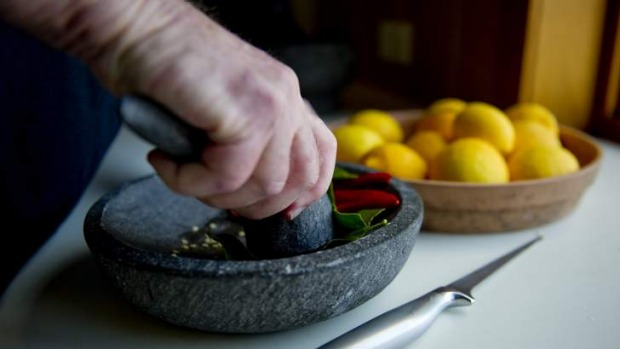 Melting pot ... Neville Bleakley grinds home-grown kaffir lime leaves with chilli using traditional Balinese mortar and ...