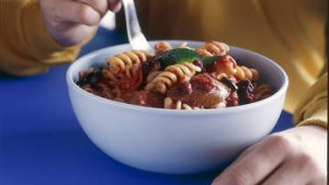Spiral pasta with sausage, tomato and olives.