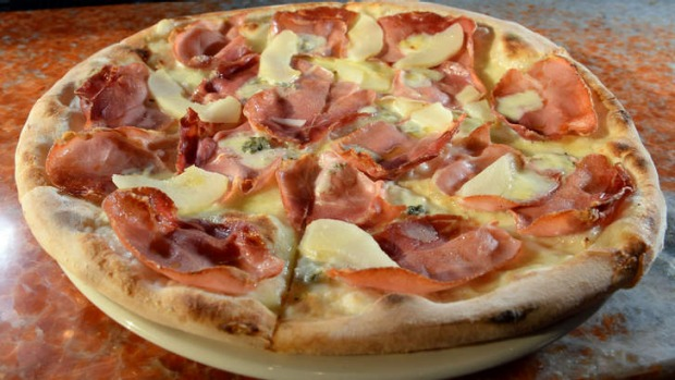 Smoky speck pizza scattered with pear and gorgonzola.