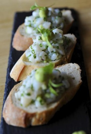 Scallop tartare on toast with avocado and wasabi.