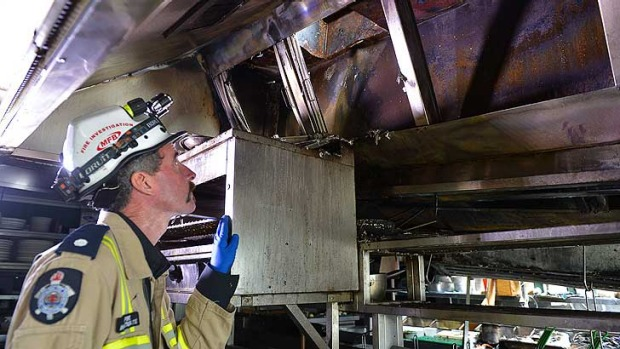 Fire station officer Damian O'Toole shows the kitchen extractor vent where the fire started.