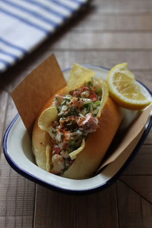 A mini lobster roll with celery, lemon and mayo.