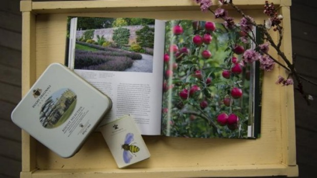 A copy of <i>Highgrove: A Garden Celebrated</i>, some fruit blossom, a tin of Duchy Originals biscuits, and a pack of ...