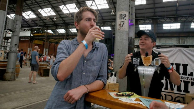 Cider fan Duncan Bell enjoys a drink while Cider Australia president Sam Reid looks on.
