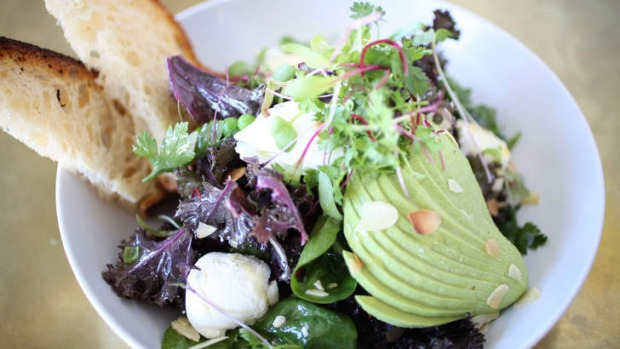 The breakfast salad includes greens, avocado and almond flakes.