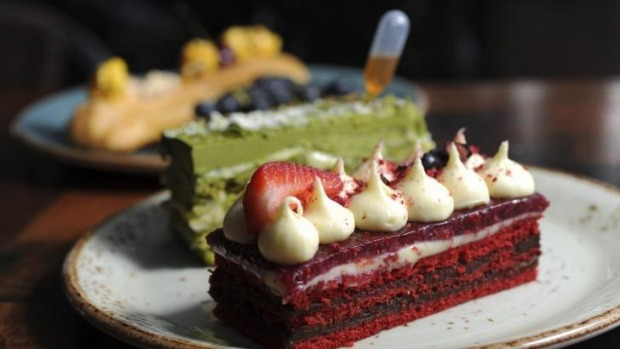 A selection of Patissez cafe's cakes, including at front a red velvet cake with Callebaut chocolate ganache, cream ...
