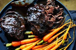 Braised beef cheeks with baby carrots.