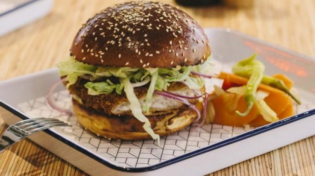 Panko-crumbed flounder burger with red onion, lettuce and lime aioli in a brioche bun.