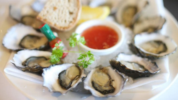 Oysters served with mignonette dressing and a miniature Tabasco bottle.