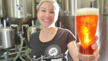 Jayne Lewis from Two Birds Brewing holds a glass of the award-winning Sunset Ale.