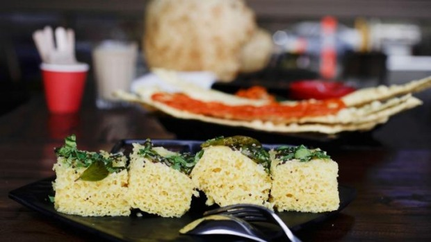 Khaman dhokla, in the foreground, is a steamed cake sprinkled with mustard seeds and curry leaves.