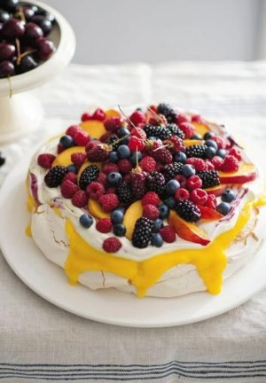 Peach and Rasberry Pavlova is smothered in seasonal berries, lemon curd and mascarpone.