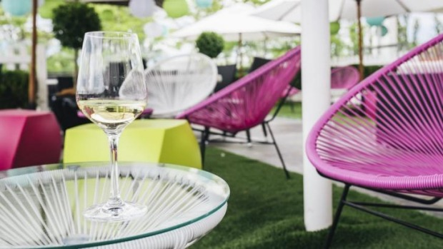 Sip cocktails while lounging on pink string chairs under shady umbrellas.
