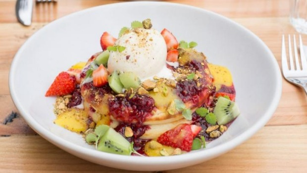 Buttermilk hotcake stack with raspberry compote, lemon curd, fruit salad, pistachios and vanilla bean ice-cream.