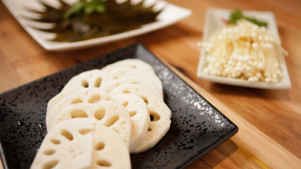 Sides include seaweed, lotus root (front) and enoki mushrooms (right).