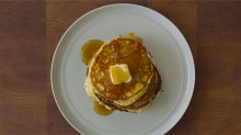 Buttermilk pancakes with butter and maple syrup.