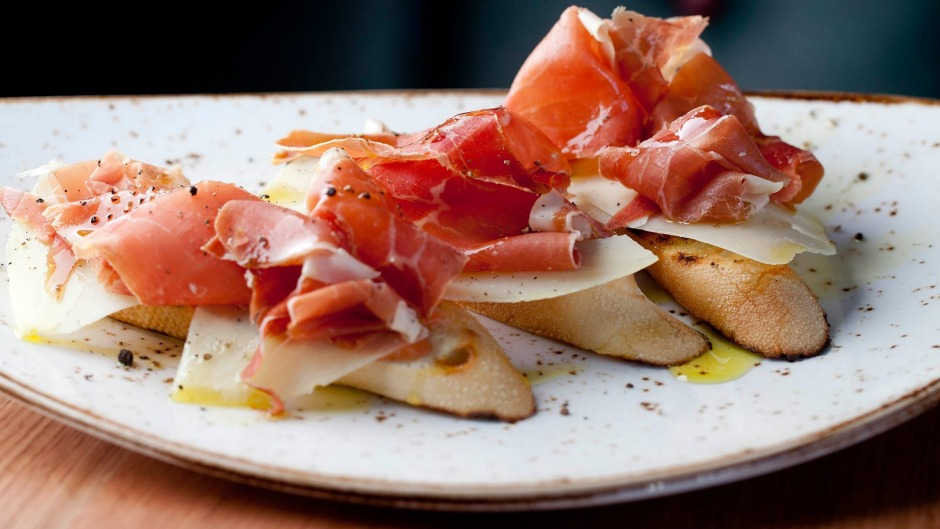 Baguette slices rubbed with tomato and olive oil, topped with manchego and jamon from Chato Tapas.
