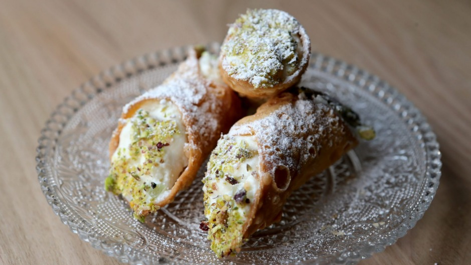 Cannoli stuffed with ricotta and dipped in pistachio is a Sicilian dessert staple.