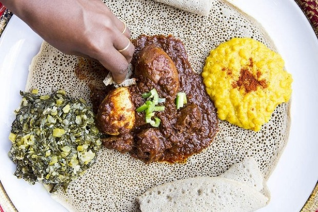 Sauteed silverbeet, slow-cooked chicken curry and turmeric-yellow split peas on injera at Saba's in Fitzroy.