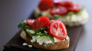 Ricotta cheese on toast with sliced tomatoes and rocket