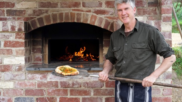 Matthew Evans pulls a pizza out of Dennis the brick oven.