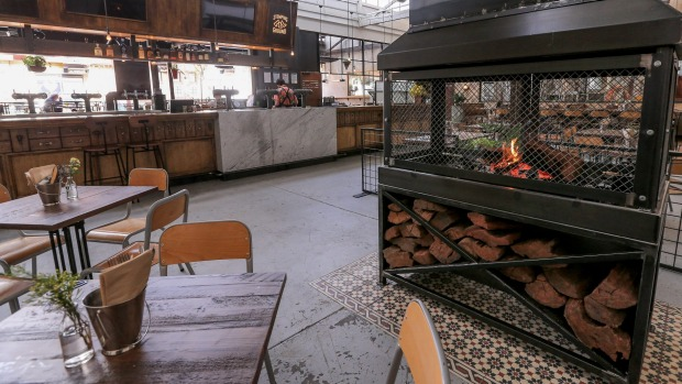 The industrial metal fireplace is the only thing allowed to smoke at Stomping Ground Beer Hall.