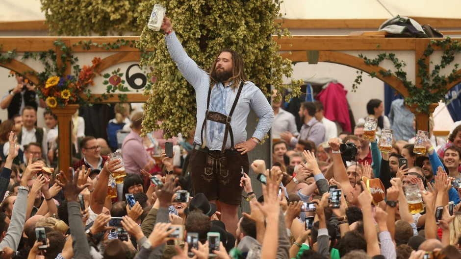 Visitors raise their glasses to toast the start of 2016 Oktoberfest festivities in the Hofbraeu tent.