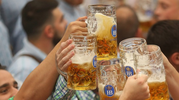 Oktoberfest visitors cheer with the traditional one-litre beer mugs.