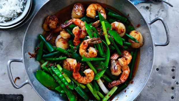 Neil Perry's spicy stir fried prawns and scallops with garlic stems, spring onions and snow peas.
