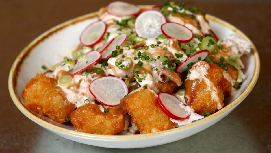 Tater tots topped with blue cheese dressing, radish and smoked chicken.
