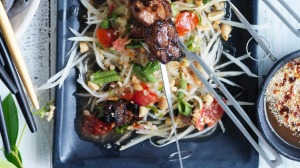 Green papaya salad used as a bed for grilled pork skewers.