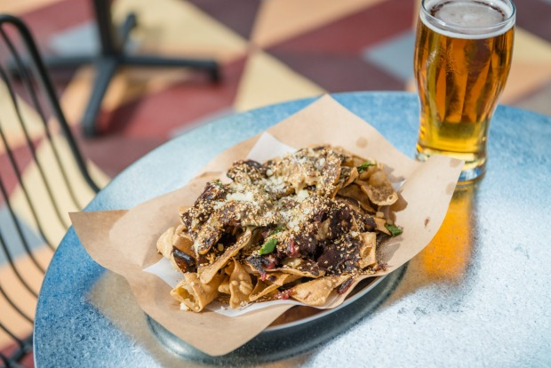 Beer and nachos with brisket mole served at Good Heavens above Fancy Hank's in Melbourne.