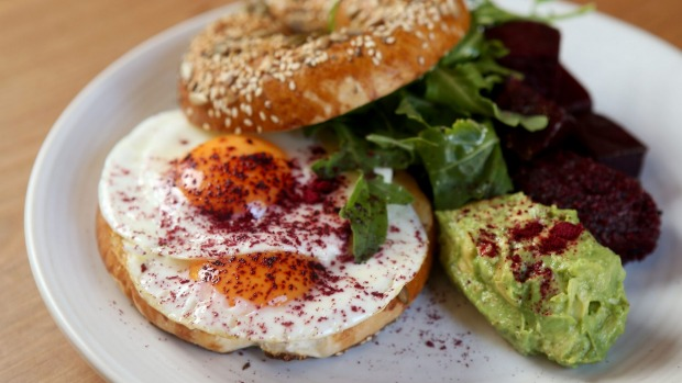 Gluten-free bagel with fried egg, sherry-roasted beetroot and smashed avocado.