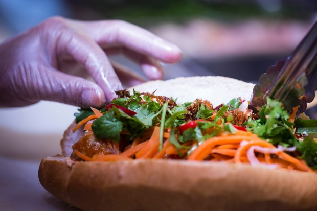Step 4: Add the remaining banh mi fillers including pickled carrot and radish, fresh coriander, cucumber slices, and ...