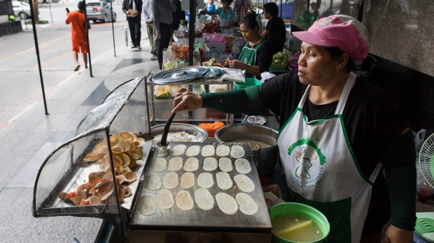 A vendor cooks crepes on a hotplate at a food stall in Phaya Thai, Bangkok.