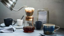 Preparing a filter coffee using the pourover method with a Chemex flask and gooseneck kettle.