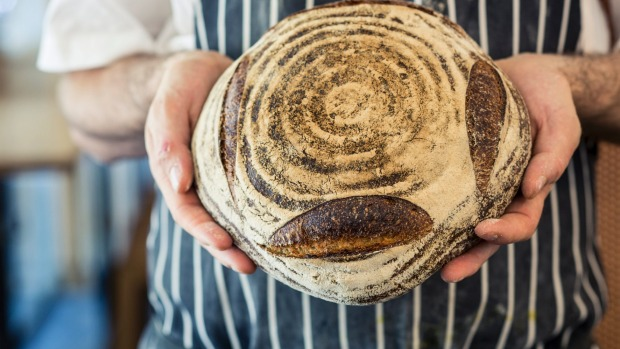 Michael James with one of his loaves of bread made from spelt flour milled at Tivoli Road bakery in Melbourne.