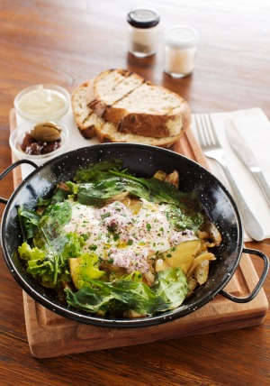 Green Shakshuka on a wooden board with olives and grilled sourdough at Shuk Cafe.