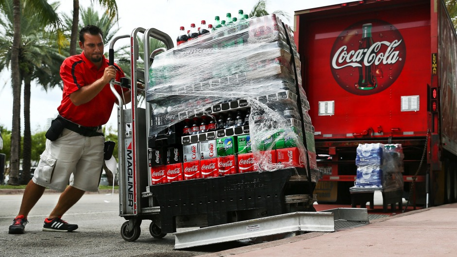 An employee delivers cases of Coca-Cola in Miami Beach, Florida.