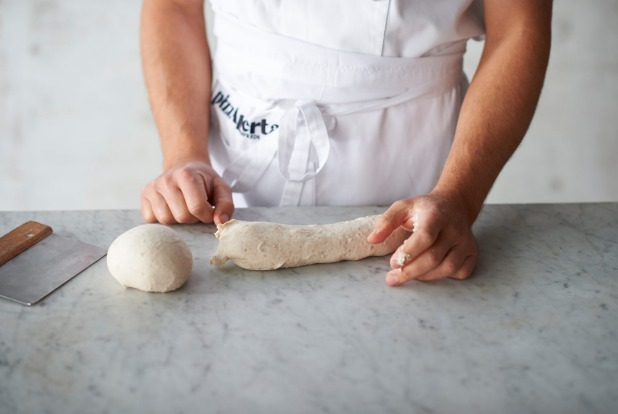 Shaping the dough step 3: Pinch the dough underneath the formed ball to separate it from the long piece of dough.