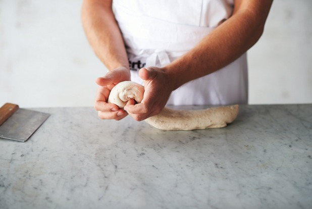 Shaping the dough step 2: The dough will feel soft, airy and malleable. Take the piece of dough at one end and, using ...