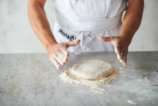 Shaping the base step 4: Place the dough ball, still bottom side up, on a small mound of flour and turn it over in the ...