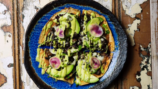 Tlayuda is like a plate-sized tortilla crispbread topped with black bean puree.