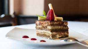 A retro tiramisu with white chocolate twirls and dots of coulis.