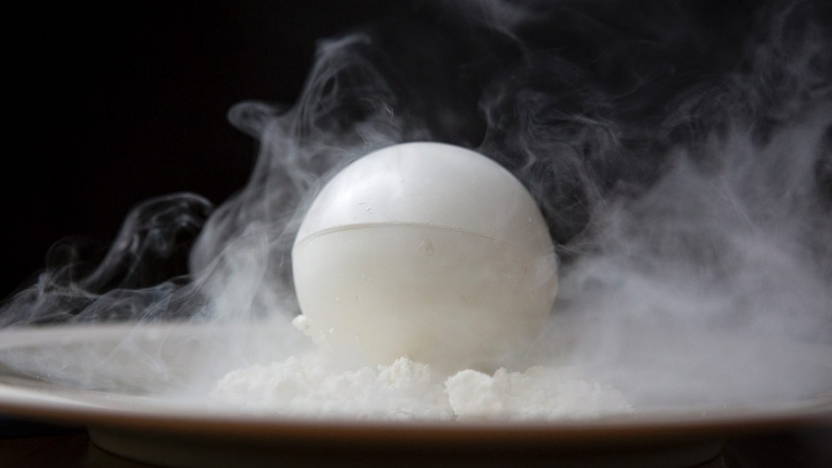A white chocolate sphere contains coffee-soaked cake and whipped vanilla cream.