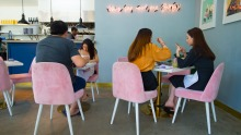 Baby's petite interior features pink neon and soft, baby-pink chairs.