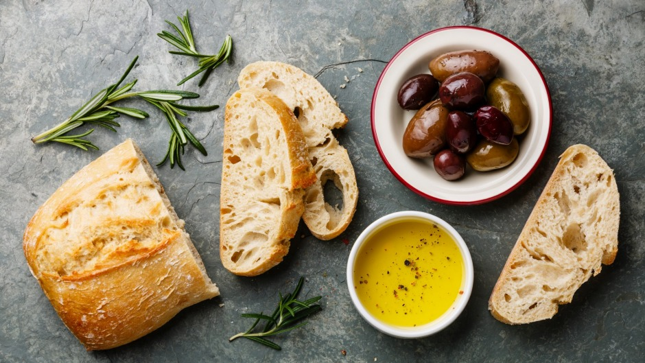 Fresh ciabatta with olive oil and olives.